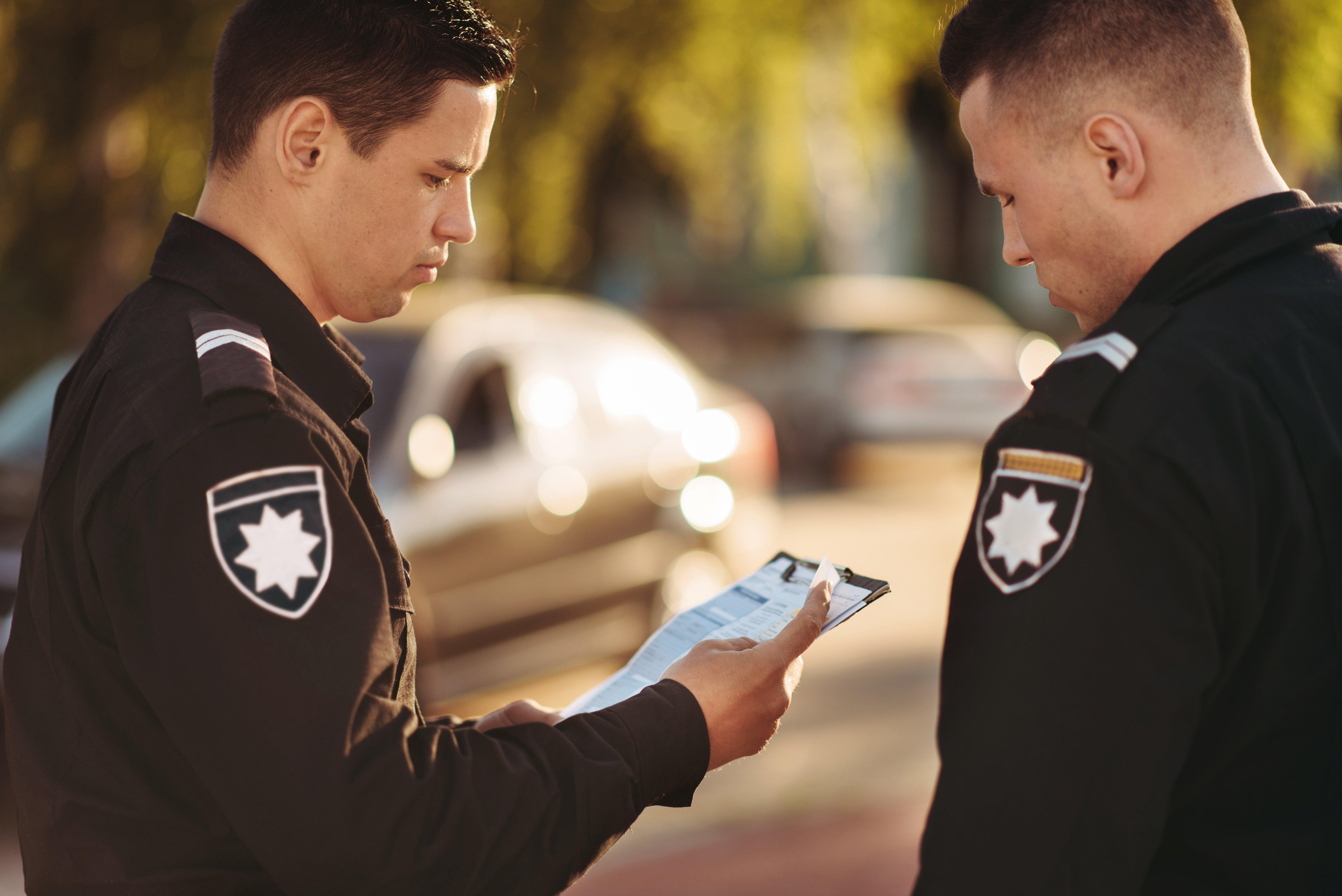 cops-in-uniform-stop-the-car-on-road-R6GCKF7